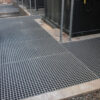 Grey QuartzGrip GRP Open Mesh Grating installed to cover drainage trenches