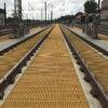 Yellow QuartzGrip Standard GRP Open Mesh Grating installed between railway tracks at a NWR depot