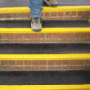 Black and yellow QuartzGrip anti-slip Stair Tread Covers installed on bicks steps