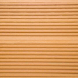 Close-up of RecDeck teak composite decking boards showing the slip-resistant grooved texture