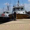 Photo taken on a sunny day showing the RNLI pontoon at Mistley Marina resurfaced using beige QuartzGrip GRP min i mesh marina decking