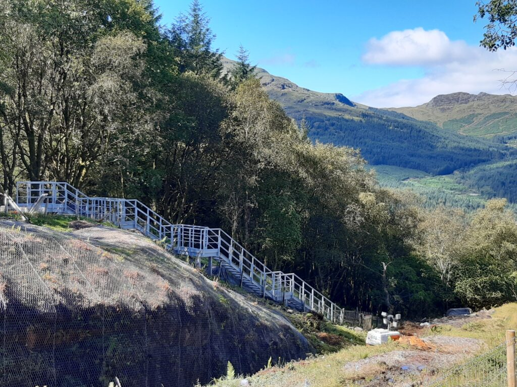A long GRP embankment staircase winding down to a track in Scottish Highlands