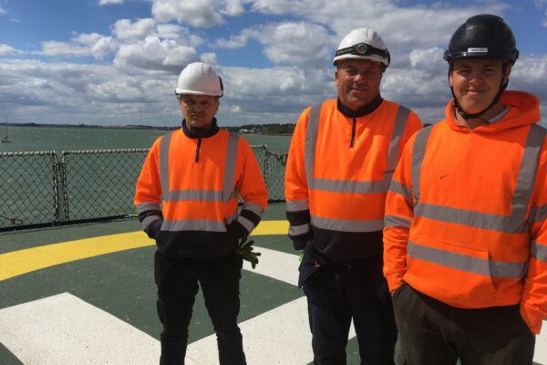 Three members of one of Step on Safetys installation teams on the deck of a Trinity House vessel