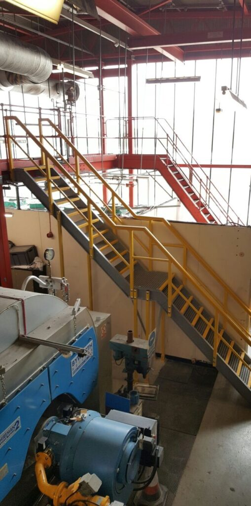Multi-storey access staircase going up to a mezzanine floor in the plant room at Colchester Hospital
