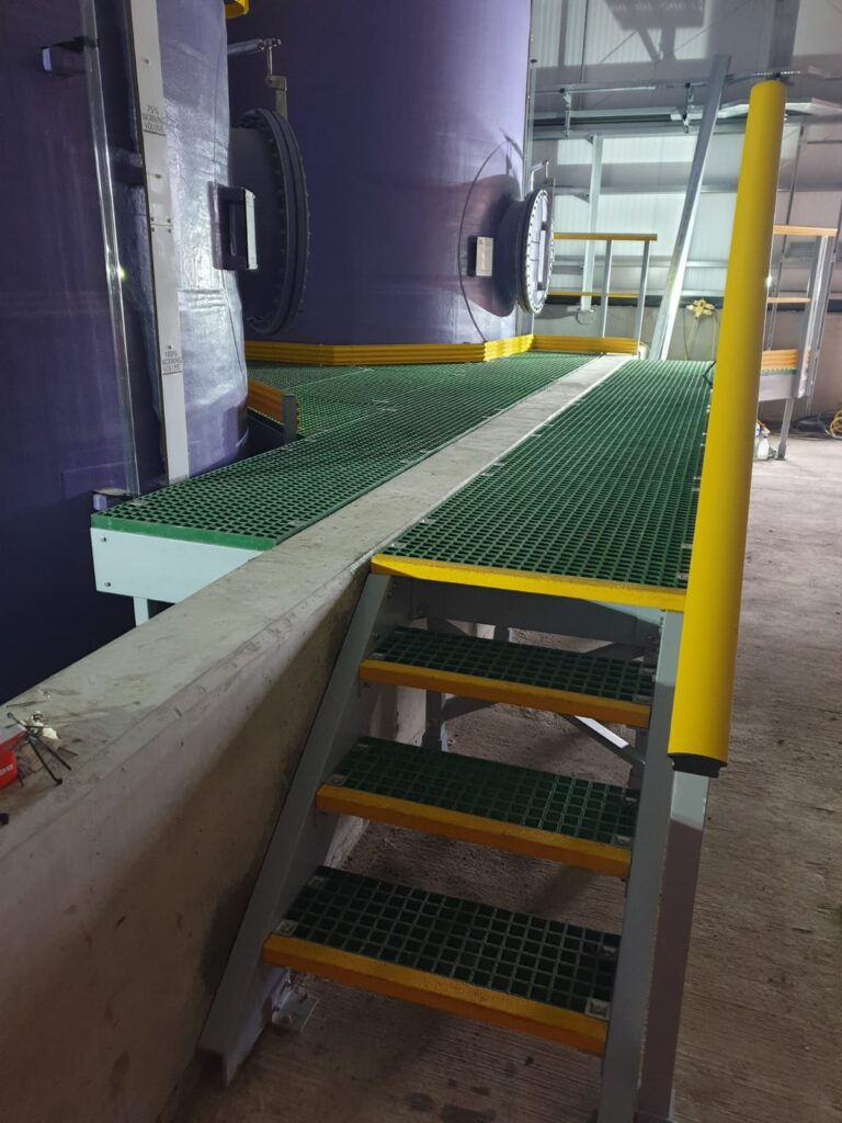 Access platform and bund floor at whitehillocks water treatment works. Steps and floor are made using QuartzGrip GRP standard open mesh panels in green. Hellow stair nosing, handrails and kickplate highlight the hazardous areas
