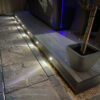 Night time shot of narrow Antique Wood composite deck the small lights setinto the side illuminating a flagstone path beside it