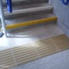 Corduroy tactile flooring at the foot of a staircase to warn those with visual impairment of the trip hazard
