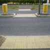 Inline blister tactile flooring at a road crossing to warn those with visual impairment of the potential hazard