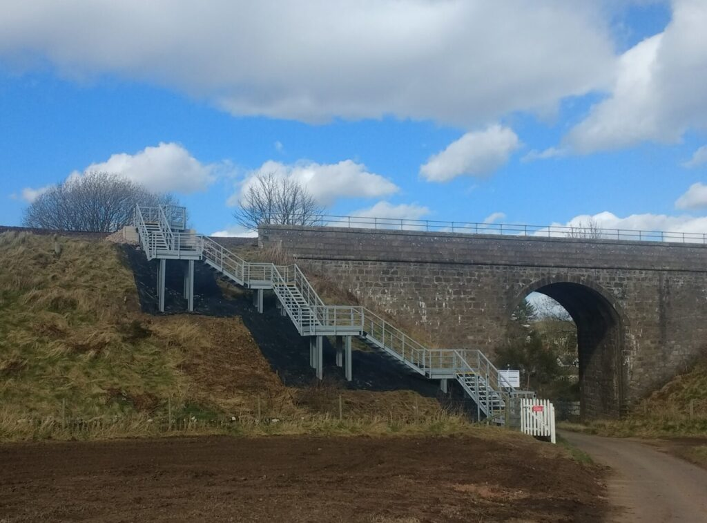 Photo shows and embankment staircase leading from a country road up to railway tracks. There are six landings to accommodate the the topography at the site at Stonehaven.