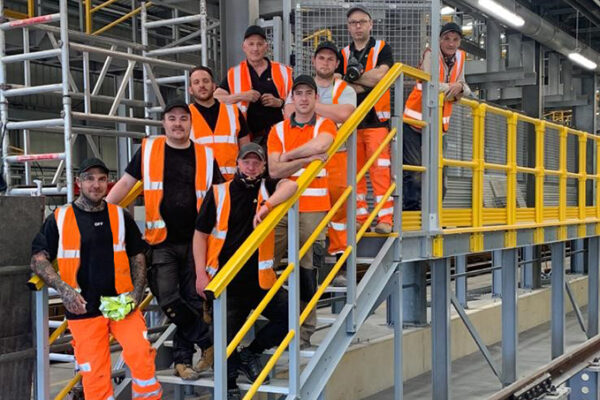 A shot of the Step on Safety team in orange hi-vis standing on the GRP steps at the end of the maintenance platform they have just completed